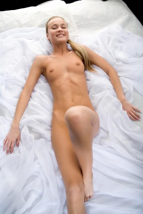 Молоденькая голая девушка нежится в белом шифоне