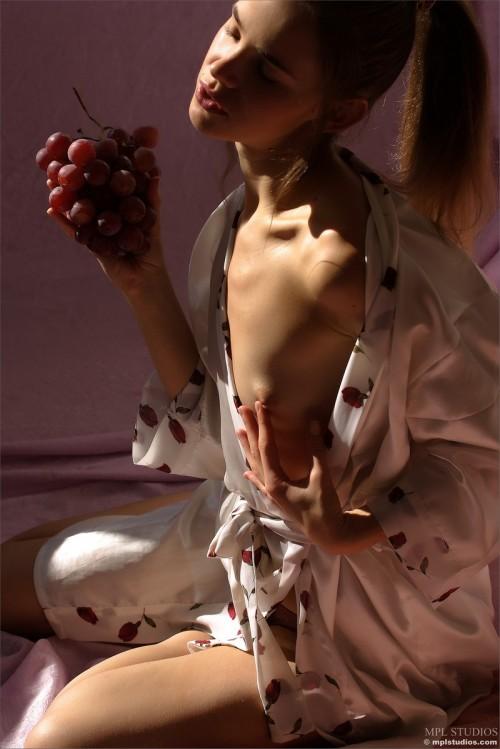Юная красавица нежится голая среди виноградных гроздей