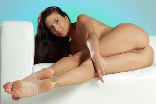 Длинноногая брюнетка позирует на белом диване