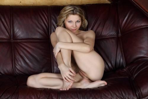 Белокурая кудряшка кувыркается на кожаном диване