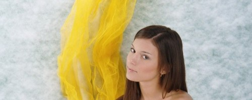 Красавица на фоне желтого фатина устроила эрофотосессию