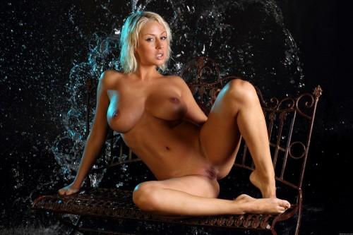 Мокрая блондинка под брызгами воды без одежды