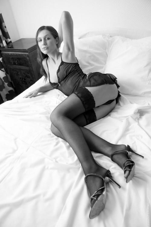 Красотка в необычном черном белье на белой постели