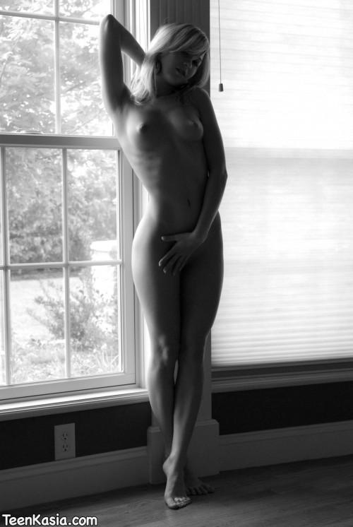Озорная девчонка на ч/б фотосесии в оконном проеме ню