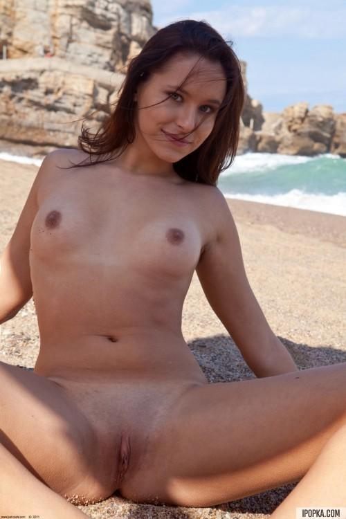 Брюнетка обнаженная нежится на морском пляже