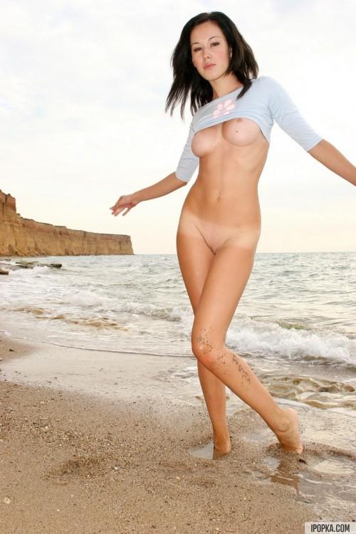 Красотка брюнетка на морском берегу озорничала голышом