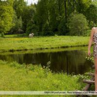 Секси брюнетка показывает голую попку на фоне озера