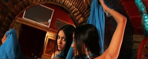 Молоденькая брюнетка в синем наряде позирует перед камерами