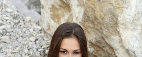 Длинноногая брюнетка раскрывает вагину на скалах