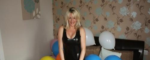 Сексуальная зрелая дамочка на больших каблуках и латексном платье