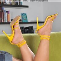 На салатовом диване яркая девочка снимает свою желтую блузку