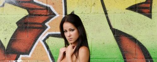 Длинноволосая брюнетка позирует голой на фоне граффити