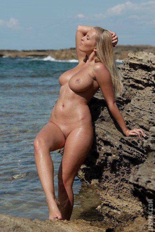 Голая прелестница с красивым бюстом на пляже играет с большим камнем