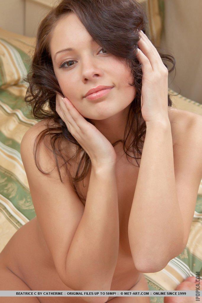 Голая девушка позирует у себя дома на кровати