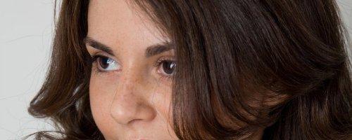 Соблазнительная темноволосая девушка показывает всю себя у мраморной стены