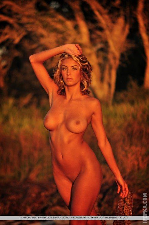 Горячая девушка с красивой грудью светит щелочку, лежа на заснеженной полянке