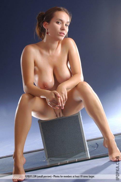 Мокрая телочка без лифчика сидит на прозрачном столе