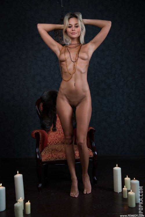 Голая блондиночка с красивой попкой на фото раздевается при свечах