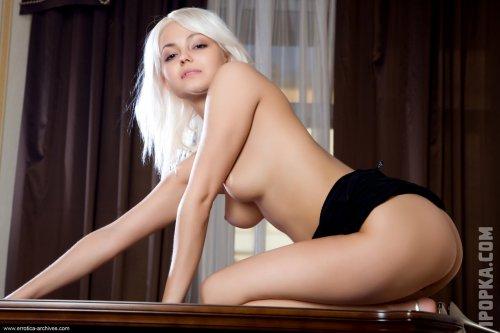 Нежная блондинка показывает свою аппетитную попку, лежа на столе