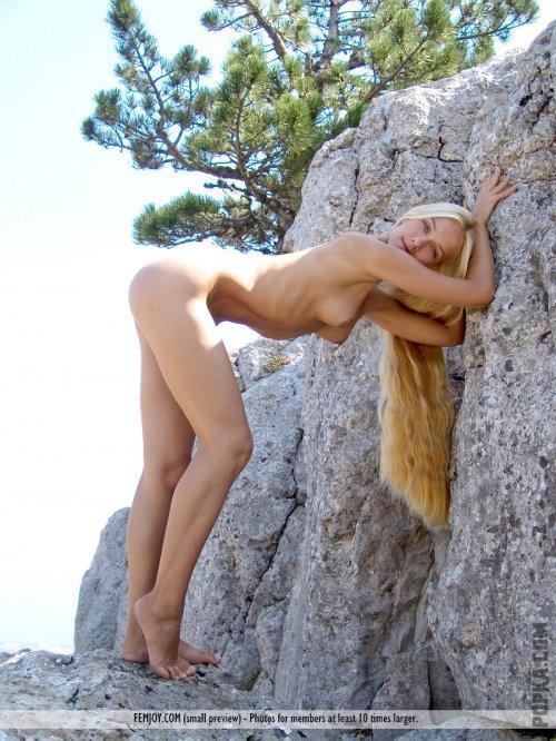 Голая девка показывает всю себя рядом с камнем