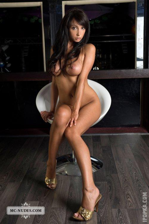 Обнаженная красавица позирует на крутящемся барном стуле