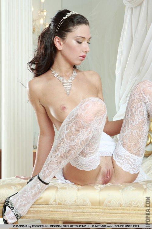 Прелестная девушка в белых кружевных чулках обнажила свою роскошную фигуру