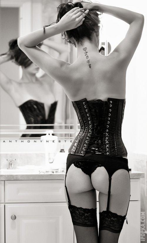 Симпатичная женщина на фотографии обнажила горячие ноги в чулках, стоя на фоне окна