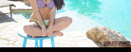 Горячая брюнетка в бикини позирует у воды красивые фотки