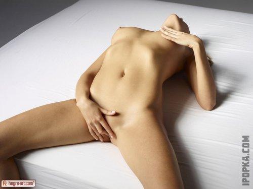 Полностью голая молодая телка с маленькими сиськами и лысой киской на фото