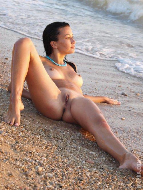 Полностью голая девушка на пляже светит сиси, киску и попу для эро фото