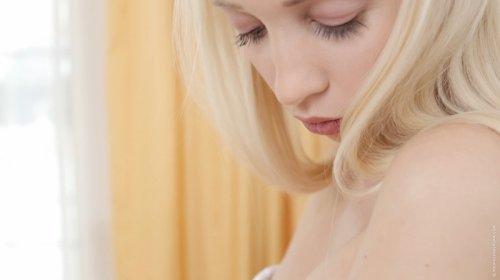 Молодая блондинка ласкает соски и мастурбирует киску на фото
