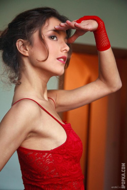 Стройная девушка в красном нижнем белье очень красиво разделась
