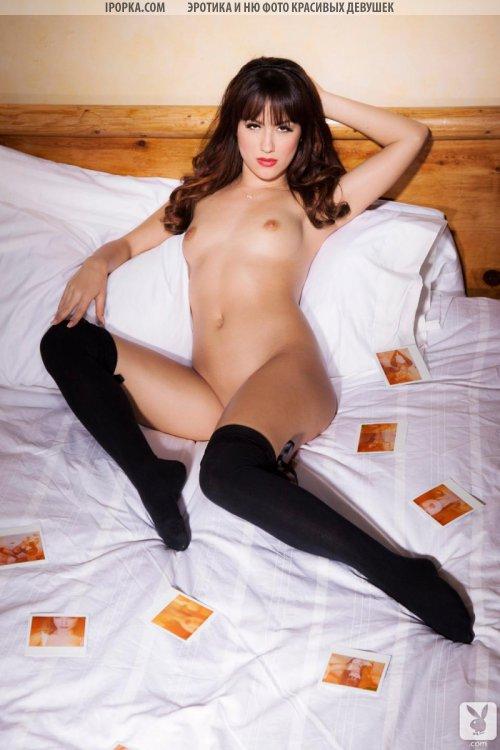 Знойная брюнетка с голой попкой в черных чулочках лежит в постели