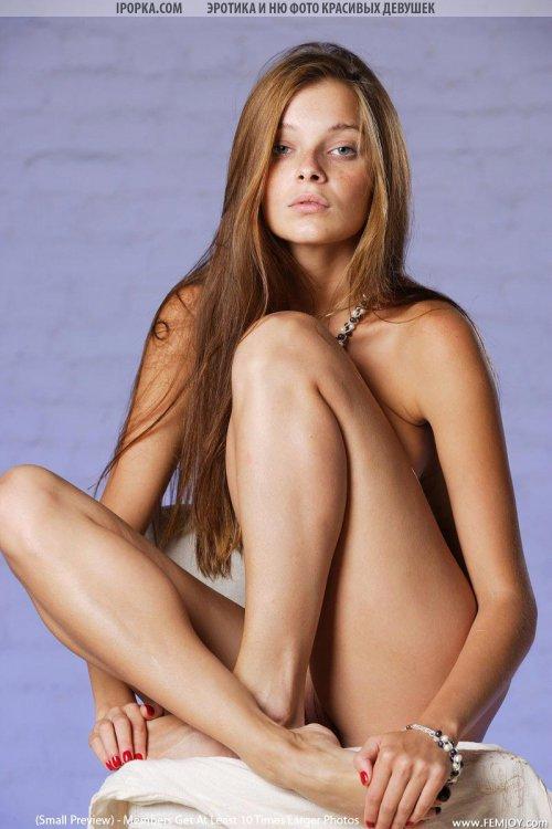 Симпатичная телка с длинными волосами красиво позирует обнаженной