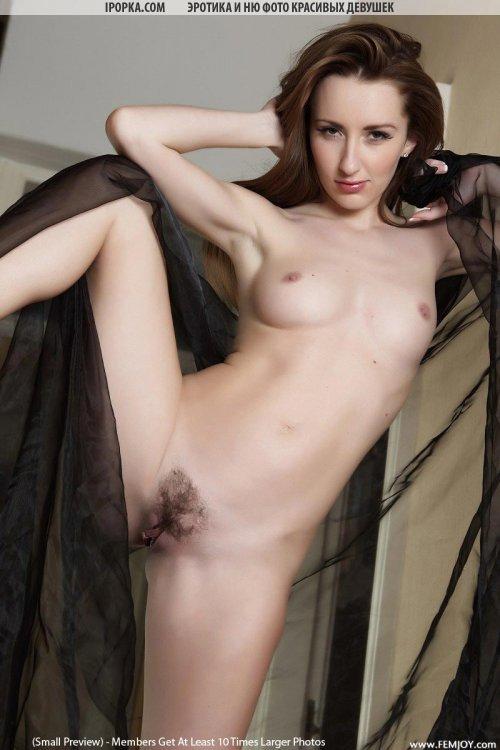 Обнаженная девушка хвастается красивым телом и мохнатой вагиной