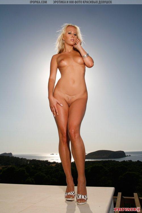 Красивая блондинка стоит голышом на фоне расцвета
