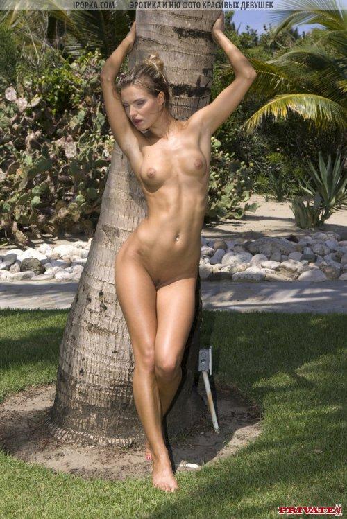 Совсем молодая горячая блондинка стоит голенькая на фоне пальм