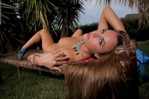 Дикая фигуристая красотка позирует среди пальм