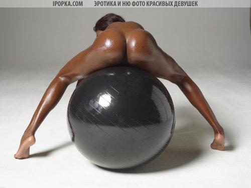 Шикарная мулатка в масле позирует на гимнастическом мяче