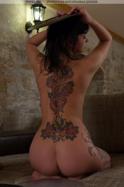 Брюнетка обнажается и показывает свои красивые тату на спине