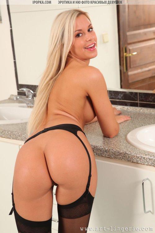 Гламурная блондинка в черных чулках снимает с себя трусики