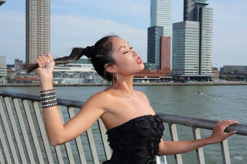 Развратная азиатка позирует голышом на фоне небоскребов