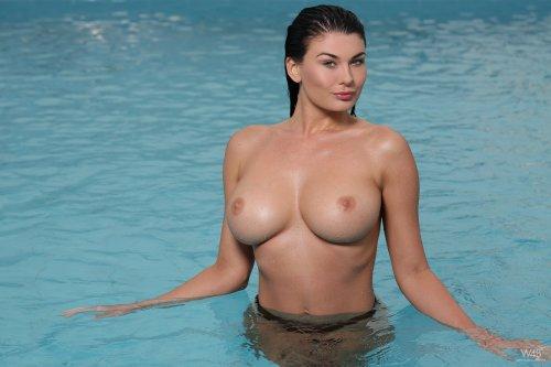 Сногсшибательная красотка с большой грудью у бассейна